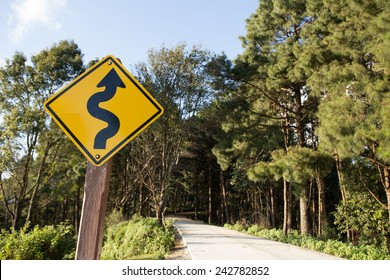 winding road sign,yellow winding road ahead sign in pine wood mountain street