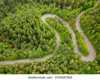 Winding road through the forest, from high mountain pass, in summer time. Aerial view by drone. Romania
