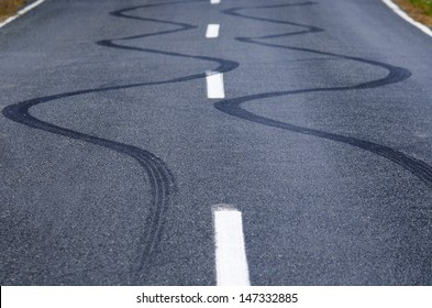 Winding skid marks of a vehicle on a street road.