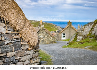 Winding street with several restored thatched cottages in Garenin or Gearrannan Blackhouse Village, Isle of Lewis, Outer Hebrides, Scotland