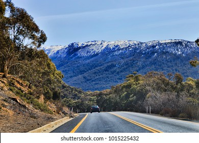 WInding thredbo road in Snowy mountains national park leading to THredbo town popular ski resort Australia. Beautiful sunny winter day with snow covered rocks of mountains ranges and snow-gum trees.