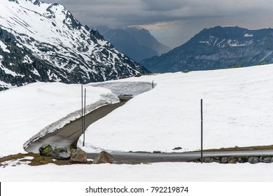 Winding and twisting road with heavy snow deposited on the sides at Susten Pass, Switzerland.