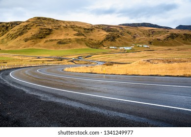 Winding Wet Hillside Road in Iceland on a Cloudy Autumn Day. A Farm at the bottom of a Mountain is Visible in Background.
