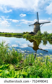 Windmill across water in Kinderdijk district popular tourist destination with it's scenic fields, ponds, canls and windmills near Rotterdam, Holland.