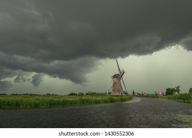 Windmill against a green sky below the base of a severe thunderstorm in The Netherlands. The green color of the sky is indicative of large hail.