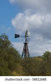 Windmill against puffy white clouds with greenery in foreground