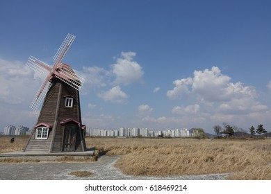 a windmill and arbor against blue sky