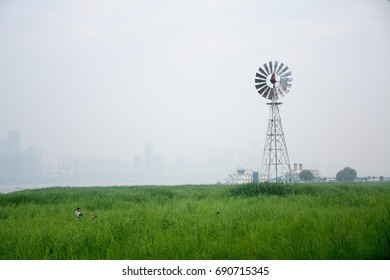 Windmill beside the river and grass field