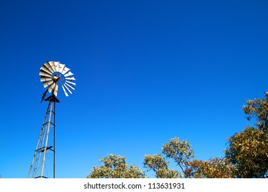 Windmill with blue sky and bush