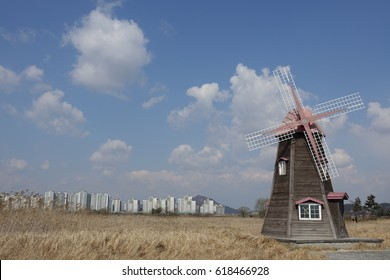 a windmill and buildings against blue sky