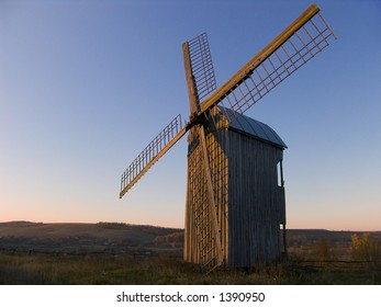 Windmill in a countryside on sunset, sky background