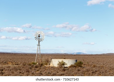 Windmill with a dam in the dry field of the Central Karoo District.