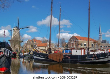 Windmill De Roode Leeuw and antique ships in canal. Turfsingel Gouda, the Netherlands.