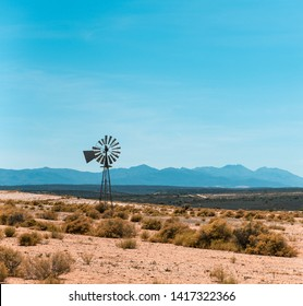 Windmill in a dry karoo landscape in South Africa with clear blue skies and mountains in the background