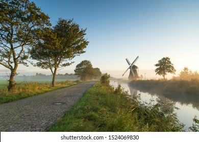 Windmill during a foggy, autumn sunrise in the Dutch countryside. Krimstermolen, Zuidwolde.