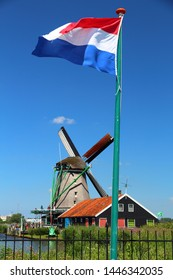 Windmill and Dutch flag in Netherlands. Old industrial architecture in Zaanse Schans rural area in Zaandam.