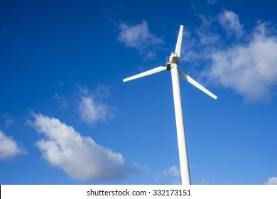 windmill for electric power production against blue sky