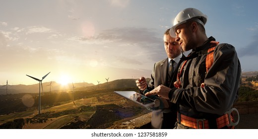 Windmill engineer and businessman planing new ecology project. they standing and looking in tablet. Around wind generators and beautiful landscape