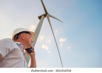Windmill engineer talking on the phone on windmill and sky background.  A man in a helmet supervises the operation of the electric windmills.