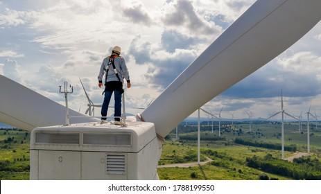 Windmill engineer wearing PPE standing on wind turbine - Shutterstock ID 1788199550