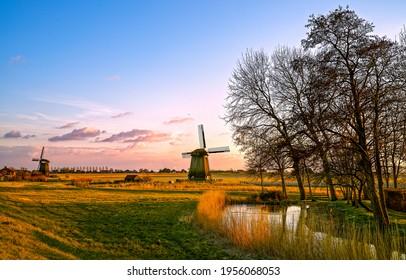 Windmill farm at dawn in Holland. Sunrise windmill farm scene. Windmill at dawn - Shutterstock ID 1956068053