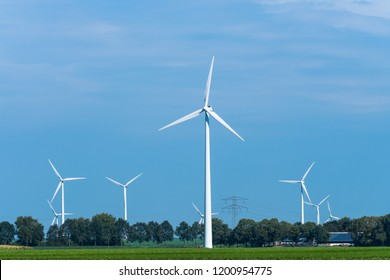A windmill farm located in an agricultural landscape. In the background there is a farm. One windmill stands in the middle. The others stand in the background. Also available in video.