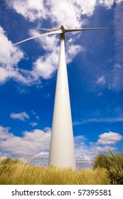 Windmill in a field against a blue sky and clouds, alternative energy source