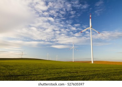 Windmill, field landscape with cloudy blue sky