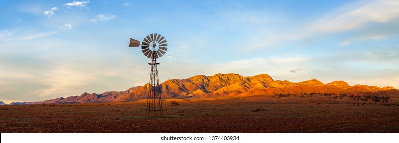 A windmill with the Flinders Ranges behind it in the Australian outback. Flinders Ranges National Park, South Australia, Australia.