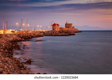 Windmill and fortified lighthouse in Rhodes town marina pier.