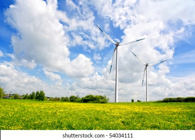 Windmill with fresh green grass and blue sky in spring