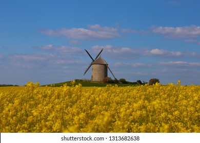 Windmill in front of a rapeseed field in Normandy, France.