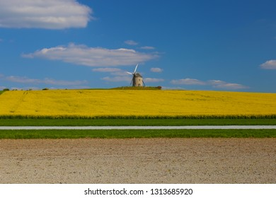 Windmill in front of a rapeseed field, road and agricultural land. Normandy, France.