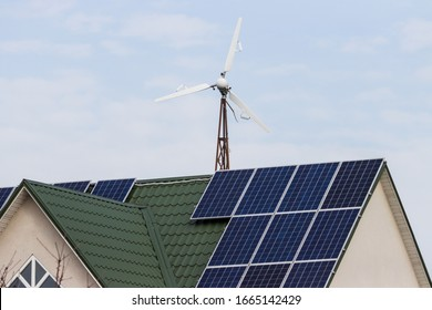 windmill and home with solar panels