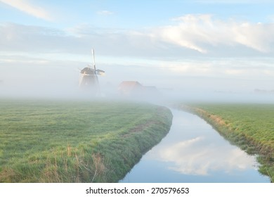 windmill in morning fog by river, Holland