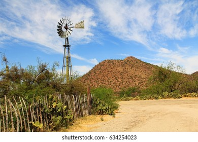 Windmill, mountain and butterfly garden along a fence on the La Posta Quemada Ranch with copy space in Colossal Cave Mountain Park in Vail, Arizona, USA near Tucson.