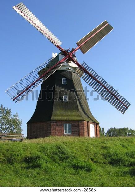 A windmill on a green hill.