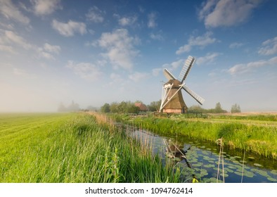 windmill on green meadow by river, Holland