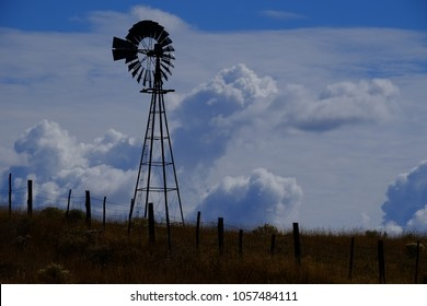 Windmill on hillside in countryside rural America with sky and clouds