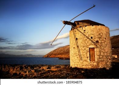 Windmill on sunset in a Greek island
