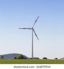 windmill Pinwheel wind turbine wind farm on landscape with blue sky and cornfield