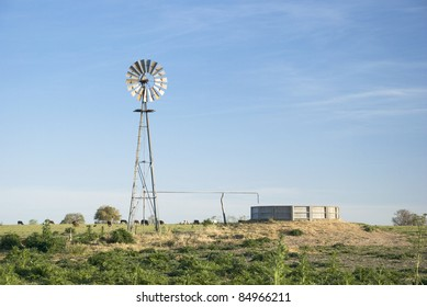 A windmill for pumping water and a concrete tank in the country. Some cows are grazing in the background.