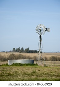 A windmill for pumping water and a metallic tank in the country.