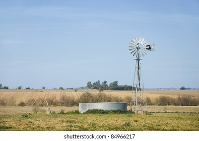 A windmill for pumping water and a metallic tank in the country. Province of Entre Rios, Argentina.