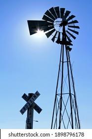 Windmill and railway crossing sign in Kingman, Arizona. Road 66. Windmill covering the sun. Light beams.