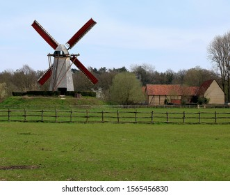 a windmill with red blades in Bokrijk, Belgium