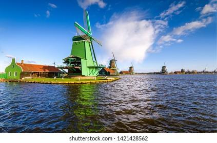 Windmill river farm landscape. Windmill farm river in Holland. Dutch windmill farm at river. River windmill farm landscape