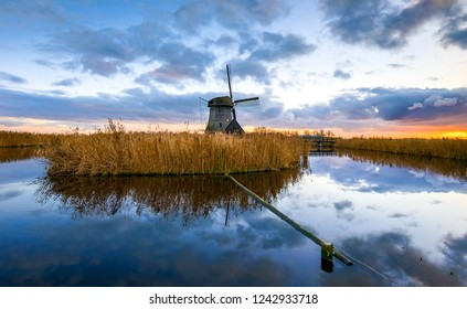Windmill river reflection sunset view. Sunset windmill river landscape. Windmill river sunset scene. Sunset windmill river reflection