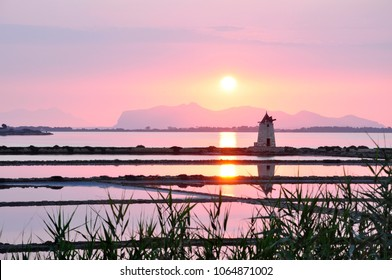 a windmill for salt production in sunset with the island of Mozia near Trapani in the west part of Sicily