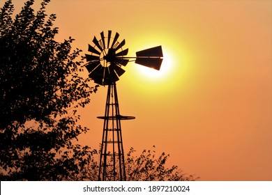 A Windmill silhouette at Sunset with a colorful sky and the Sun north of Hutchinson Kansas USA out in the country.